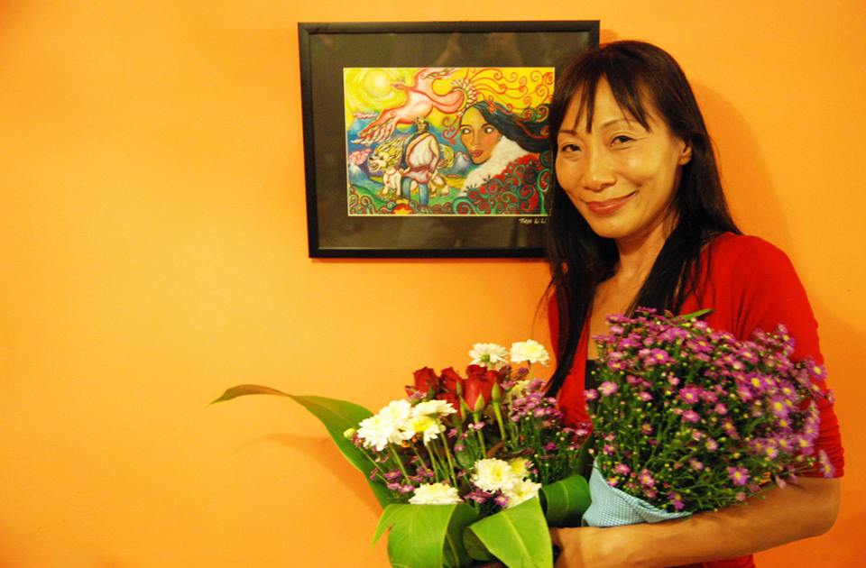 Artist Li Li Tan with her painting in background